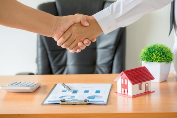 Side view hands of agent and client shaking hands after signed contract buy new apartment.